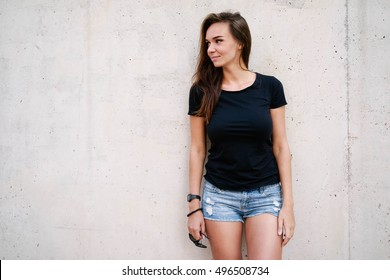 A hipster girl with long brown hair wearing a blank black t-shirt is looking aside while standing on a light blue wooden fence background on a street.Horizontal mock up. Empty space for text o design.