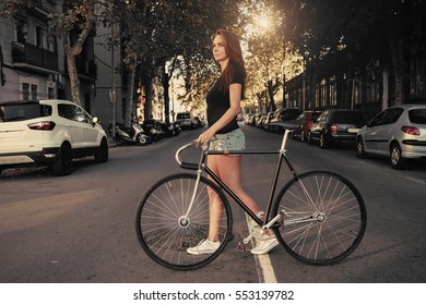 A hipster girl with a long brown hair wearing a blank black t-shirt and blue jeans shorts is holding a handle bar of a fixed gear bicycle while crossing the road on a sunny street background.