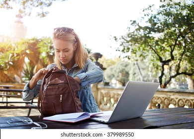 Hipster girl looking for something in the bag while sitting outdoors at the table with open net-book, young female searching the pen in rucksack for writing an essay on a notebook from laptop computer