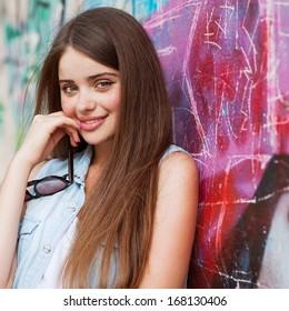 hipster girl outdoors stands near a graffiti wall