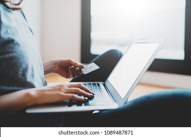 Hipster girl paying online via internet on laptop computer while is sitting at home. Woman booking room hotel with credit card in web site online. Secure data and online payments concept