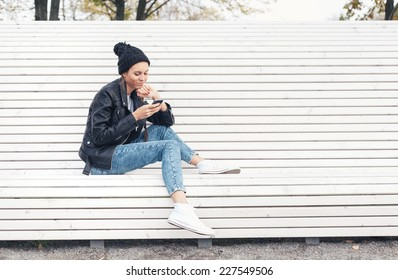 Hipster girl with phone reading text on a white bench in the park.  Outdoors lifestyle portrait of young woman