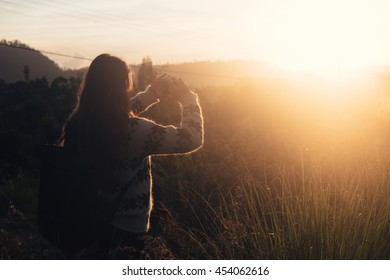Hipster girl photographer with backpack at sunrise. Explore sunrise, outdoor Bali mountain travel. Travel woman at sunrise. Sunrise girl silhouette. Explore mountain sunset. Travel adventure in Bali