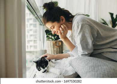 Hipster girl playing with cute cat, sitting together at home during coronavirus quarantine. Stay home stay safe. Isolation at home to prevent virus epidemic. Young woman with cat in modern room