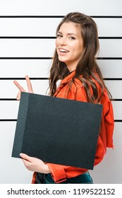 hipster girl posing with empty prison board and showing peace sign in front of police line up