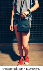 Hipster Girl Posing In Front Of Closed Night Club Door In red Trainers With Black Leather Handbag