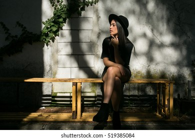 hipster girl posing in a garden with a hat and heavy style
