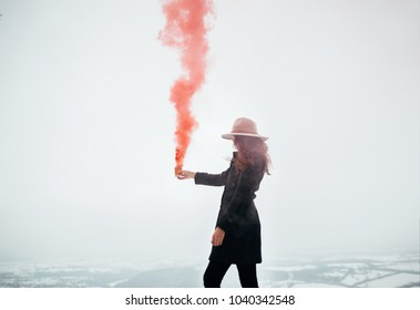 Hipster girl with red smoke bomb send smoke signal. Emergency flare signal