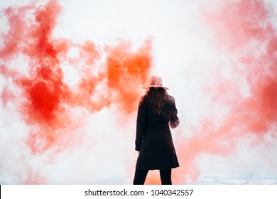 Hipster girl with red smoke bomb