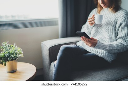 Hipster girl relaxing at home on sofa drinking coffee and using modern smartphone device, attractive woman chilling at cozy home interior chatting at social network, copy space for design or text mess