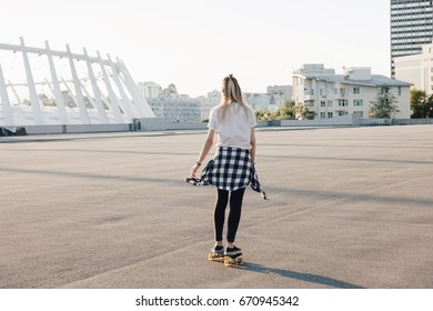 Hipster girl riding skate board in the city