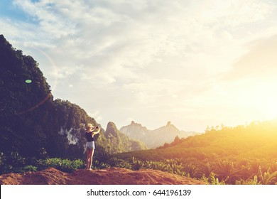 Hipster girl is shooting video of beautiful sundown on cell telephone, while is standing against Amazon scenery background with copy space. Female tourist is taking photo with mobile phone camera