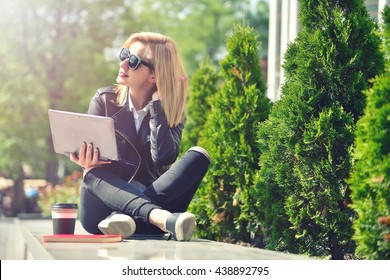 hipster girl sitting with a laptop and straightens hair