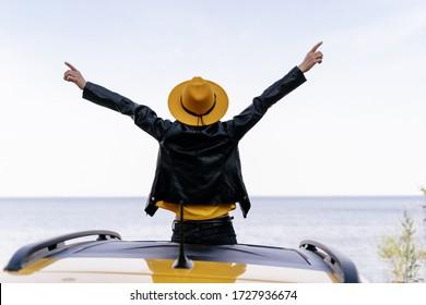 Hipster Girl sitzt auf der Rückansicht des Gelben Autos. Frau mit aufgewachsenen Waffen beim Ocean Summer Freedom Concept. Trendy Female Genießen Sie die Roadtrip Nature River oder Lake von der Spitze des Fahrzeugs aus. Wochenendleben
