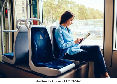 Hipster girl sitting in tram using modern touchpad for chatting in social networks with friends via free wifi connection, young woman reading e-book downloaded on portable pc in public transport