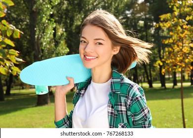 Hipster girl with skateboard in park