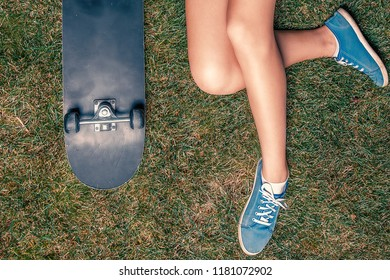 Hipster girl with skateboard resting on green grass in park with her legs crossed