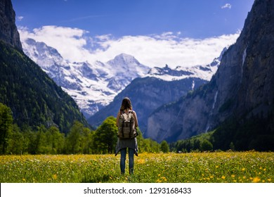 Hipster girl standing in the Lauterbrunnen Valley in the Jungfrauregion,Switzerland, alps. Mountains everywhere.