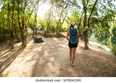 Hipster girl summer. Single beautiful backpacker girl on a campsite. Green trees, water and tents in the background.  blue backpack, girlish hat, shorts, tanned long legs. Holidays concept. Tourist