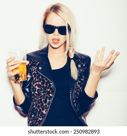 Hipster girl in sunglasses and black leather jacket  drinking beer, not isolated on white background