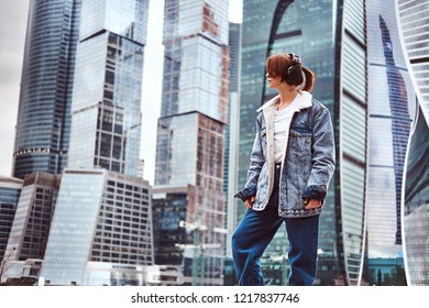 A hipster girl with tattoo on her face trendy dressed wearing headphones listening to music in front of skyscrapers in Moskow city at cloudy morning.