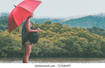 A hipster girl traveler standing in the peaceful misty forest on rainy day by the river, holding red umbrella and caring a backpack - Retro vintage film look with some fine film grain added.
