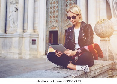Hipster girl with trendy look is reading electronic book on portable touch pad, while is sitting outside the museum. Beautiful woman is watching movie on digital tablet, while relaxing after strolling