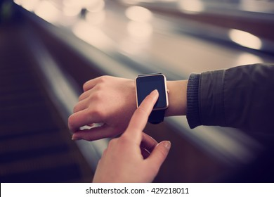 Hipster girl use smart wrist watches mobile app riding escalator in metro.Always stay connected.Big blank empty screen for mobile application logo.Stylish gold touchscreen device