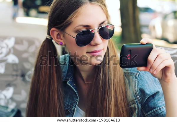 Hipster girl uses a smartphone. Photo toned style instagram filters