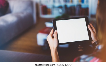 Hipster girl using tablet technology in home atmosphere, girl person holding computer with blank screen on background bokeh, female hands text on relax holiday, mockup templates gadget, blur concept