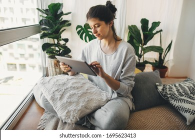 Hipster girl using tablet, working from home during quarantine. Stay home stay safe. Isolation at home to prevent virus epidemic. Home office. Young woman studying at window in modern room
