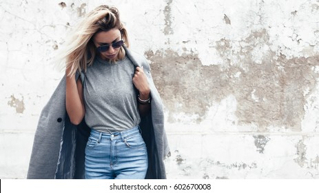 Hipster girl wearing blank gray t-shirt, jeans and coat posing against rough street wall, minimalist urban clothing style, mock up for tshirt print store