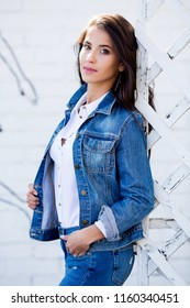 Hipster girl wearing blank white shirt, jeans and jeans jacket posing against street wall. Minimalist urban clothing style, street fashion.