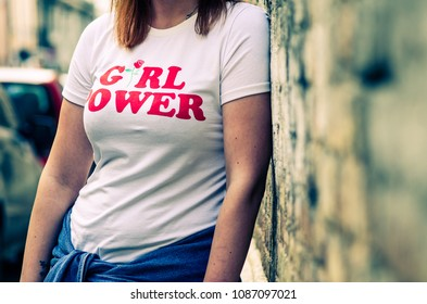 Hipster girl wearing Girl Power t-shirt posing against rough street wall, minimalist urban clothing style.