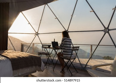 Hipster girl working with a laptop at home office in the mountains with great views