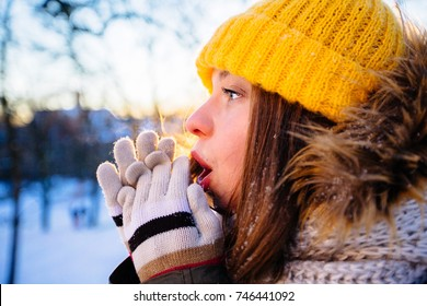 Hipster girl in yellow cup freezing in winter park in snowy sun winter day. Woman blowing on cold hands wth coloful mittens. Pictures in warm colors. Close up, side view