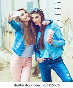 Hipster girlfriends taking a self photo on the street in fashion jeans clothes