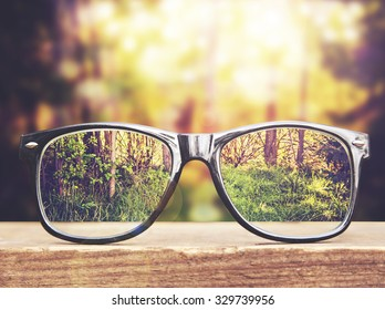 hipster glasses on a park bench or table with a forest in the background toned with a retro vintage instagram filter app or action effect