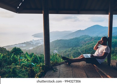 Hipster gut traveler working remote while enjoying Thailand nature landscape during summer vacations. Male freelancer using internet connection and modern devices outdoors against tropical environment