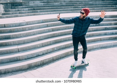 A hipster guy does selfie on his smartphone and rides on a skateboard. life style