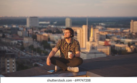 A hipster guy listens to music on headphones and drinks coffee on the roof of a high-rise building. He looks into the distance and enjoys the moment. Freelancer in search of inspiration.