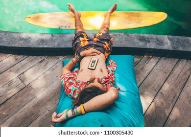Hipster guy with long hair and sunglasses in colorful board shorts and Hawaiian shirt sunbathing on bean bag next to swimming pool, relaxed, with mobile phone on his chest and feet on surfboard