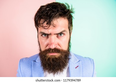 Hipster guy with messy tousled hair and long beard needs barber service. Keep hair tidy and care about hairstyle. Man bearded hipster on strict face pink blue background. Barber tips grooming beard.
