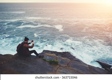 Hipster guy taking pictures of amazing landscape on mobile smart phone digital camera while sitting on a rock near the sea, beautiful sunset light create background with copy space for text message