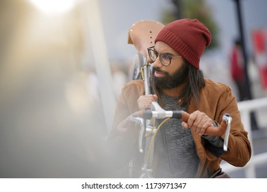 Hipster guy in town carrying fixie bicycle