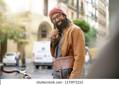 Hipster guy in town using earphones and fixie bike