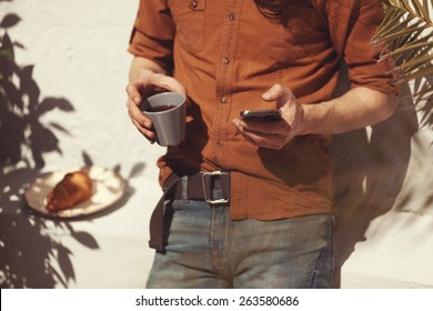 hipster guy using his smart phone outdoors and relaxing