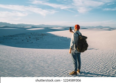 Hipster guy wanderlust making selfie on smartphone camera on breathtaking scenery of desert back view of male traveler with rucksack using telephone for making picture during journey to White sands