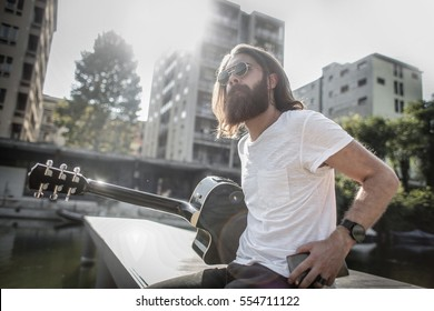 Hipster guy wearing sunglasses and holdong his guitar by the lake