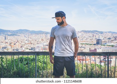 Hipster handsome male model with beard wearing gray blank t-shirt and a black snapback cap with space for your logo or design in casual urban style.Panoramic view of modern BCN city on the background
